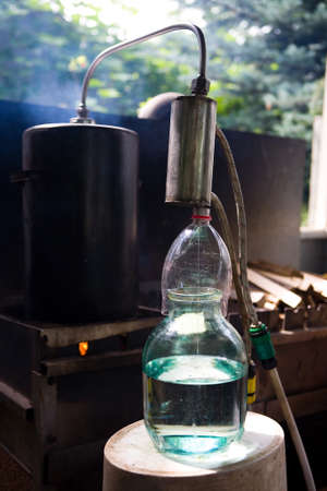 Moonshine flows from a homemade moonshine apparatus into a glass jar. Production of moonshine in Russia.