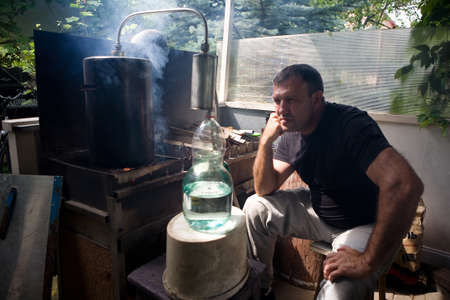 A man observes how the moonshine flows in a glass jar. Production of moonshine in Russia. 写真素材