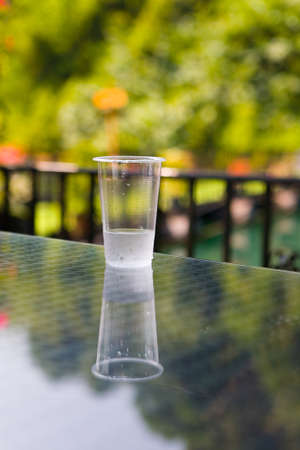 A cheap plastic cup with water is on the table. Outdoors.