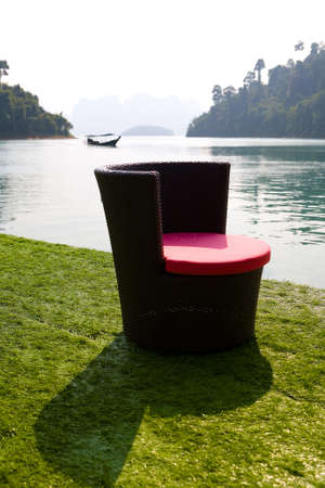 The armchair stands on the shore of the lake Cha Long, in the background floats a boat. Thailand.