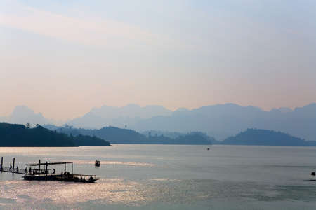 People on a small pier near the boat. Fantastic landscape of lake Cha Long at sunset.