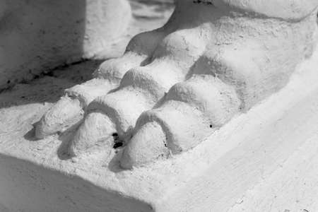 A fragment of plaster sculpture photographed close-up. Paw of a fantastic animal.