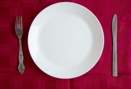 White clean plate and cutlery on the table. Cookware.