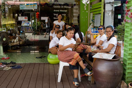 Phuket, Thailand, February 20, 2018: Employees sit at the entrance to the massage parlor and await customers.