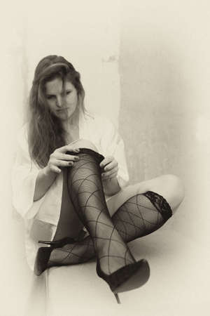 A young woman without panties pulls her knee socks. Erotica in the photo.