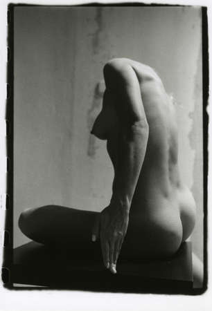 A slender naked girl without a head sits. Attention! Image contains grit and other artifacts of analog photography!