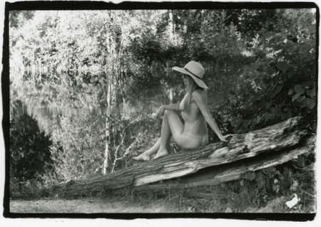 Naked girl sitting on a log near the pond. Attention! Image contains grit and other artifacts of analog photography!
