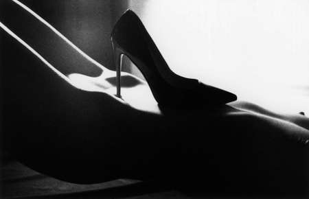 A high-heeled shoe stands on a woman's tummy. Attention! Image contains grit and other artifacts of analog photography!