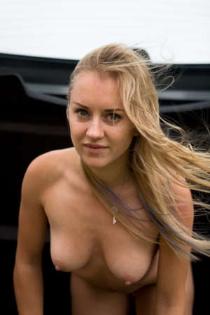 Beautiful naked blonde in the trunk of a car. The look is directed to the camera. 写真素材