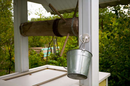 Country well with a bucket on a chain. Rural life.