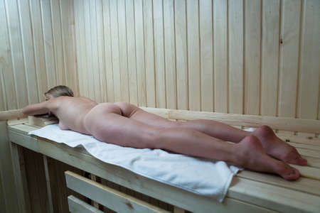 Beautiful naked slim blonde lies on a shelf in the sauna. Nude.