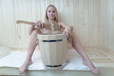 Beautiful naked natural slim blonde holds a ladle in a hand over a bucket. Nude in the sauna. Zdjęcie Seryjne