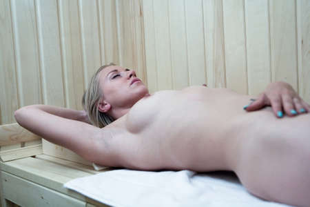 Slender beautiful naked blonde with natural breasts is steam in the sauna. Nude.