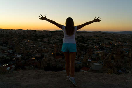 In the evening, a slender girl spread her arms in different directions. Top view of the city of Goreme at sunset. Turkish Cappadocia. Reklamní fotografie