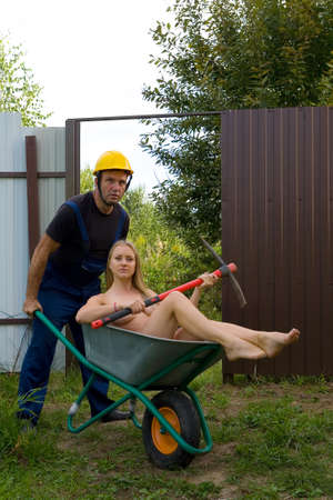 Worker in overalls and helmet transport a naked blonde in a wheelbarrow. Nude and humor.