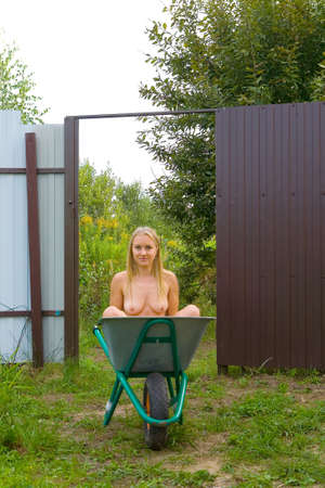 Beautiful naked slender natural blonde sits in a construction wheelbarrow. Nude and humor.