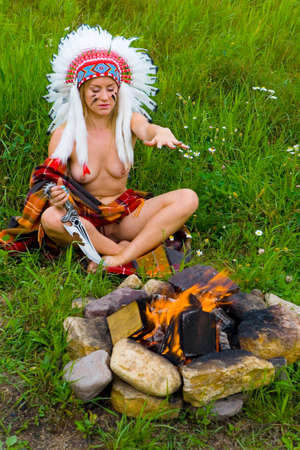 A beautiful slender naked blonde in an Native American costume sits with a knife in her hand. A bonfire burns in a stone grill nearby.