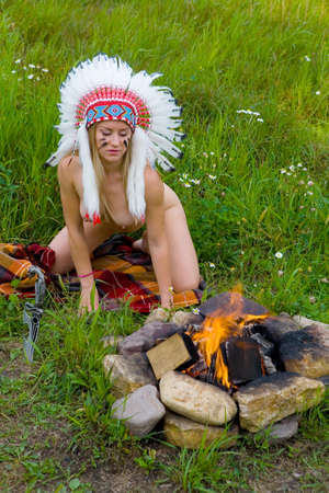 A beautiful slender blonde in an Native American costume sits next to a bonfire. Nude.