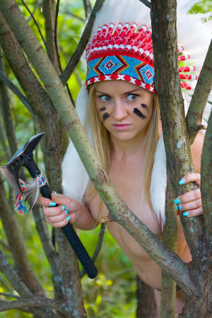 A beautiful slender naked blonde in a Native American costume with a tamahawk in her hand hides behind the branches. On open air.