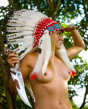 A beautiful slender naked blonde in a Native American costume with a knife in her hand peers into the distance. On open air.