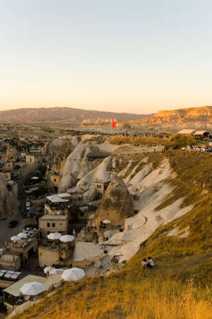 Goreme, Turkey, September 3, 2017: Evening top view of a small town. People gathered on the mountain to watch the sunset in Turkish Cappadocia.