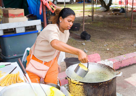 Phuket, Thailand, February 23, 2018: Thai woman cooks and sells waffles outdoors.
