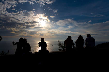 Phuket, Thailand, February 23, 2018: Silhouettes of people who watch the picturesque sunset on the sea.
