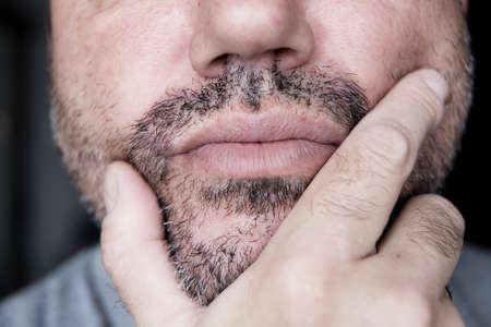 The male hand is near the unshaven chin. Thoughtfulness.