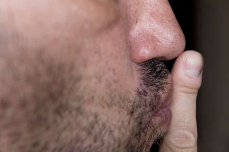An unshaven man raised his index finger to his lips. Close-up side view.