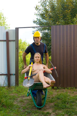 Worker in overalls and helmet carries a naked blonde in a wheelbarrow. Nude and humor.
