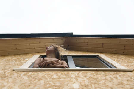 Naked blonde peeps out the window of a country house. View from below.