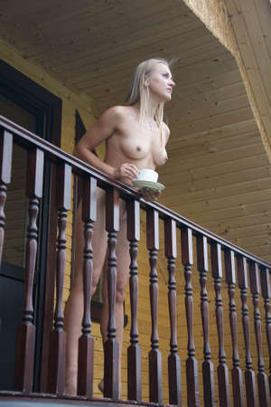 Naked slender girl stands on the balcony of a country house. She holds a cup and a plate in her hands.