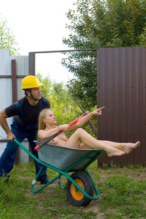 Worker in overalls and helmet carries a naked blonde in a wheelbarrow. The girl shows him the way with his hand.