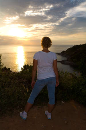 Slender natural blonde watches the sunset on the sea. Human and nature.