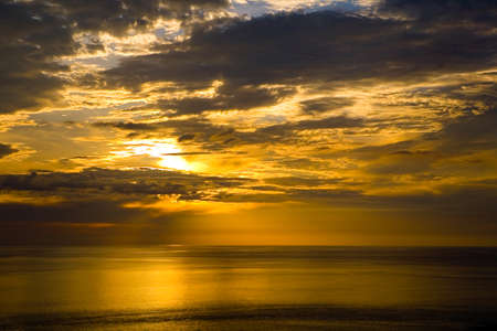 Colorful golden sunset and cloudy sky at the sea. Nature. 免版税图像