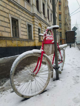 Snow covered bike stands on the street. The weather in Moscow.
