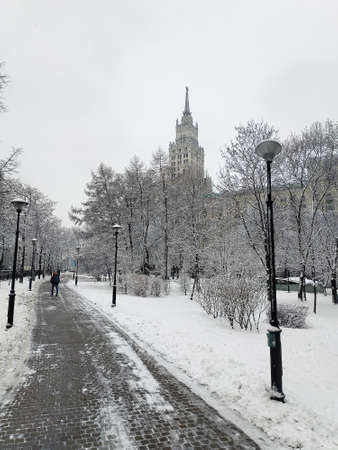 A path in a winter square against the background of a Soviet-era high-rise building. Moscow.