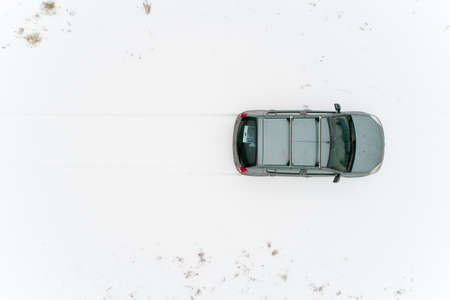 Top view on a car that stands in a snow-covered field. Nearby are human footprints. Aerial photography.