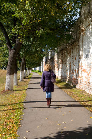 A slender natural blonde walks past an ancient wall in the fall. The view from the back. 免版税图像