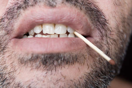 A match in the teeth of an unshaven man. Close-up.