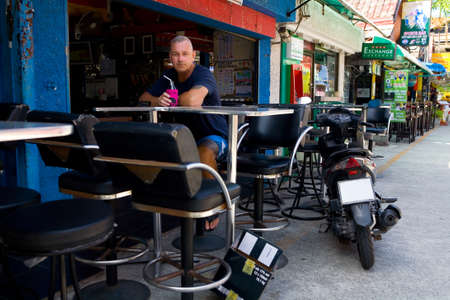 Phuket, Thailand, February 24, 2018: A European with a cocktail in his hand is relaxing in a Thai bar. Nearby is a motobike.