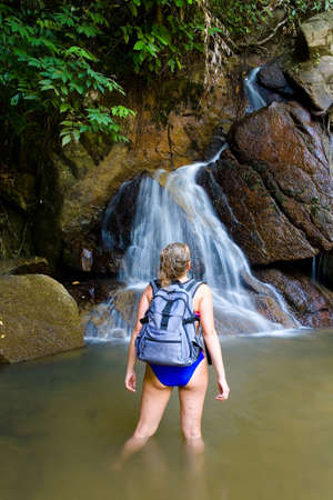 Girl tourist in a swimsuit and with a backpack admires the picturesque waterfall. The nature of Thailand. 免版税图像