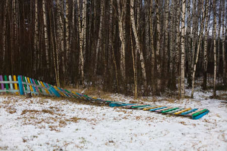 Fallen multi-colored fence of a playground at the edge of the forest. Winter in central Russia.
