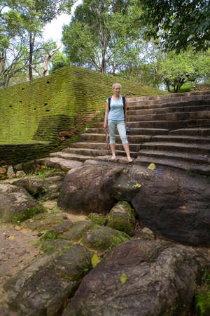 Cute natural barefoot blonde stands on the old steps. Polonnaruwa in Sri Lanka. 免版税图像