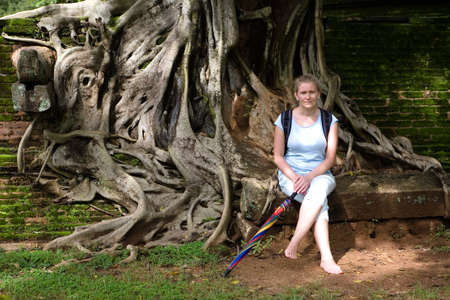 A woman crouched next to the huge tree roots in Polonnaruwa. Traveling in Sri Lanka.