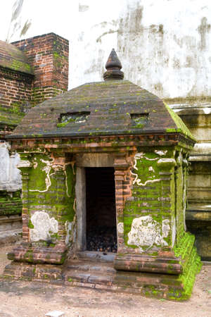 A small unusual old building in Polonnaruwa is overgrown with moss. The ancient architecture of Sri Lanka.