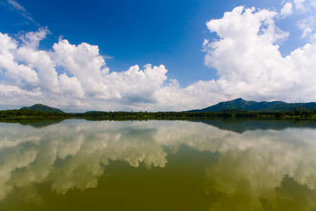 Mountains and a cloud in the sky are reflected in the lake. Beautiful landscape of Sri Lanka.