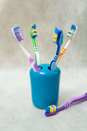 Multi-colored toothbrushes stand in a special glass. Still life.
