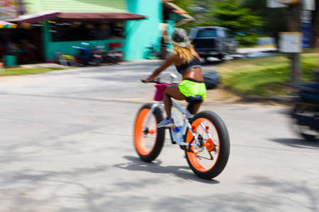 Phuket, Thailand, February 20, 2018: A beautiful slender dark-skinned woman riding a bicycle. Motion blur.