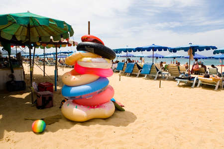 Phuket, Thailand, February 20, 2018: Inflatable circles and resting tourists on the sandy beach of Karon. 免版税图像 - 144179289